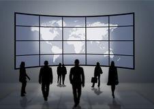 Leuteschattenbilder, die zu einer großen Weltkarte schauen Lizenzfreie Stockfotografie