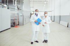 Leutetechnologen in den Masken an der Nahrungsmittelfabrik lizenzfreie stockbilder