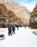 Leutetrekking auf gefrorenem zanskar Fluss Trekkers, die Taschen auf Eis ziehen Chadar-Wanderung, Ladakh Indien lizenzfreies stockfoto