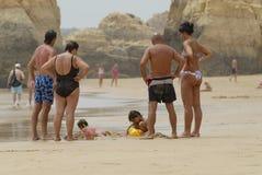 Leuteuhr scherzt das Spielen am Strand in Portimao, Portugal Lizenzfreies Stockfoto
