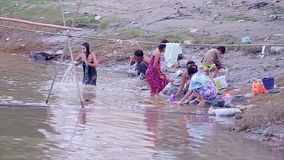 Leutewäsche und baden im Fluss stock footage