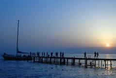 Leuteweg auf Pier auf Sonnenuntergang Stockfoto