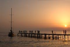 Leuteweg auf Pier auf Sonnenuntergang Stockbild