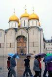 Leuteweg unter Regenschirmen durch Dormitions-Kirche Stockfoto
