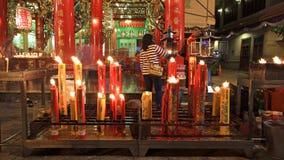 Leuteweihrauch nahe den großen Kerzen zum zu beten Stockfoto