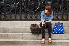 LEUVEN BELGIA, WRZESIEŃ, - 05, 2014: Niewiadoma młoda kobieta siedzi na krokach Katolicki uniwersytet z hełmofonami Fotografia Royalty Free