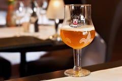 LEUVEN BELGIEN - SEPTEMBER 05, 2014: Original- exponeringsglas av Tripel Karmeliet öl i en av restaurangerna i Leuvenen royaltyfri fotografi