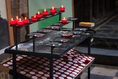 LEUVEN BELGIEN - SEPTEMBER 05, 2014: Traditionella röda stearinljus i kyrkan för St Peter ` s av Leuven Arkivbilder