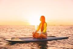 Levántese el embarque de la paleta en un mar reservado con colores calientes de la puesta del sol Relajación en el océano Fotos de archivo libres de regalías