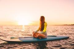 Levántese el embarque de la paleta en un mar reservado con colores calientes de la puesta del sol Relajación en el océano Imagen de archivo