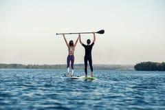 Levántese a la gente de la playa del paddleboard en el tablero de paleta Fotografía de archivo