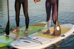 Levántese a la gente de la playa del paddleboard en el tablero de paleta Imagenes de archivo