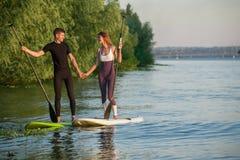 Levántese a la gente de la playa del paddleboard en el tablero de paleta Fotos de archivo