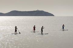 Levántese a las personas que practica surf de la paleta Imagen de archivo libre de regalías