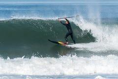 Lev?ntese a la persona que practica surf de la paleta fotografía de archivo libre de regalías