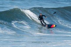 Lev?ntese a la persona que practica surf de la paleta fotografía de archivo