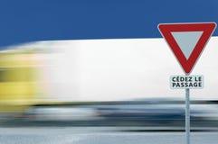 Leva o sinal de estrada de cédez le passagem do francês do rendimento, fundo borrado movimento do tráfego de veículo do caminhão fotografia de stock
