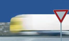 Leva o sinal de estrada do rendimento, fundo borrado movimento do tráfego de veículo do caminhão, aviso regulador do quadro verme foto de stock royalty free