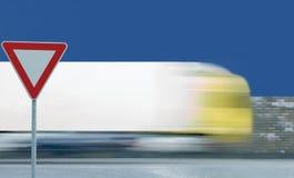 Leva o sinal de estrada do rendimento, tráfego de veículo borrado movimento do caminhão imagens de stock