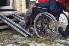 Levage d'un invalide dans un fauteuil roulant dans une maison de campagne Image stock