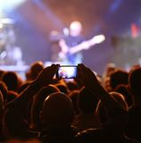 levande konsert med en gitarrist och fanen med den smarta telefonen royaltyfri foto