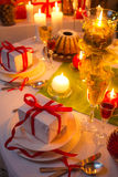 Levande ljus och gåvor lite varstans jultabellen Arkivbilder