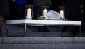 Levande ljusvaka - tre stearinljus och blommor royaltyfria bilder