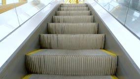 Levantamento acima na escada rolante com lados de vidro à estação de metro