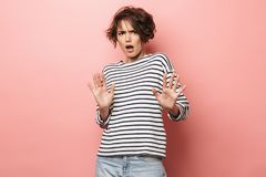 Levantamento bonito desagradado da mulher isolado sobre o fundo cor-de-rosa da parede para fazer para parar o gesto fotografia de stock