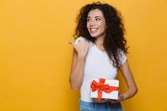 Levantamento bonito feliz entusiasmado da jovem mulher isolado sobre apontar amarelo do presente da caixa de presente da terra ar imagens de stock royalty free