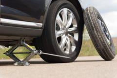 Levantamento com macaco acima de um carro para mudar um pneumático Imagens de Stock Royalty Free