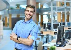 Levantamento do homem novo seguro e positivo no escritório profissional do local de trabalho com espaço imagem de stock royalty free
