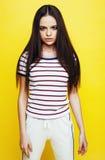 Levantamento emocional da mulher consideravelmente adolescente dos jovens no fundo amarelo, conceito dos povos do estilo de vida  Imagem de Stock