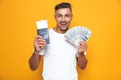 Levantamento emocional do homem isolado sobre o passaporte amarelo da terra arrendada do fundo da parede com bilhetes e dinheiro fotografia de stock royalty free