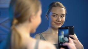 Levantamento fêmea novo para a parte dianteira do espelho, apego social do selfie das redes, divertimento video estoque