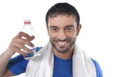 Levantamento feliz do homem do esporte incorporado com água e a toalha para o fitness center Imagens de Stock