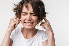Levantamento forçado desagradado bonito da mulher isolado sobre o fundo branco da parede que cobre as orelhas devido a alto fotos de stock