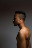 Levantamento latino do homem interno sobre uma parede cinzenta Imagens de Stock Royalty Free