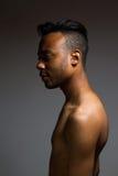 Levantamento latino do homem interno sobre uma parede cinzenta Fotografia de Stock