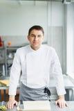 Levantamento masculino de sorriso novo do cozinheiro chefe Fotografia de Stock