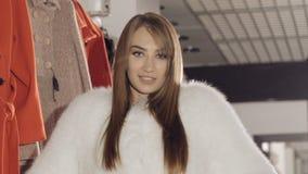 Levantamento modelo agradável no casaco de pele rico no boutique para anunciar filme
