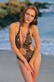 Levantamento modelo consideravelmente na praia rochosa no swimsuit Imagem de Stock