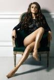 Levantamento modelo da mulher luxuosa bonita no vestido laçado preto na cadeira do rertro Retrato bonito no interior Imagens de Stock Royalty Free