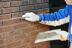 Levantamiento de muros usando la paleta de la ensambladora del ladrillo Imagen de archivo