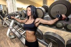 Levantamiento de pesas de la mujer en gimnasio moderno Foto de archivo libre de regalías