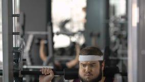Levantamiento de pesas gordo del hombre con esfuerzo en gimnasio, ejercicio de la aptitud, deseo de la pérdida de peso almacen de video
