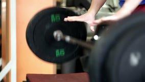 Levantamiento de pesas practicante de la mano deportiva joven del hombre en un gimnasio del crossfit almacen de video