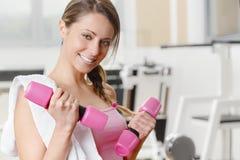 Levantamiento de pesas sonriente de la mujer joven en el gimnasio Imagenes de archivo