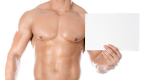 Levantamiento de pesas y publicidad: un culturista fuerte agradable que sostiene una tarjeta en blanco blanca de papel aislada en Imágenes de archivo libres de regalías