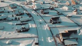 Levantamiento para arriba sobre el suburbio típico del invierno rodeado por la nieve clara blanca en la puesta del sol metrajes